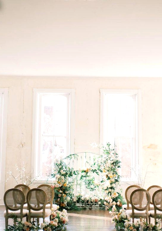 floral iron gate wedding backdrop with cane back dining chairs