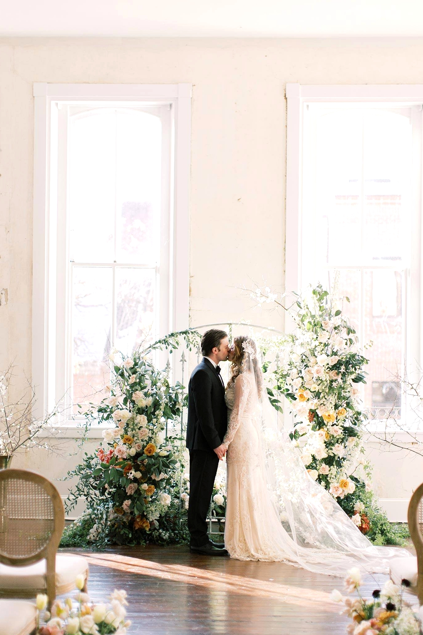 Old World wedding backdrop with a floral iron gate and bride and groom kissing