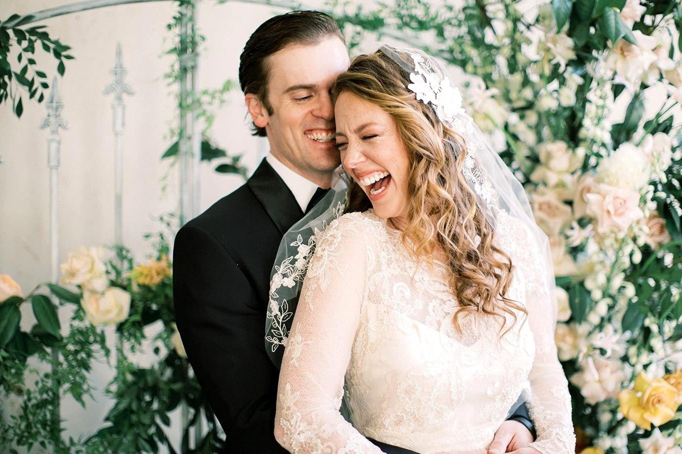 vintage inspired wedding dress with embroidered lace and pearl embellishments with a vintage lace bridal veil and a black groom tux