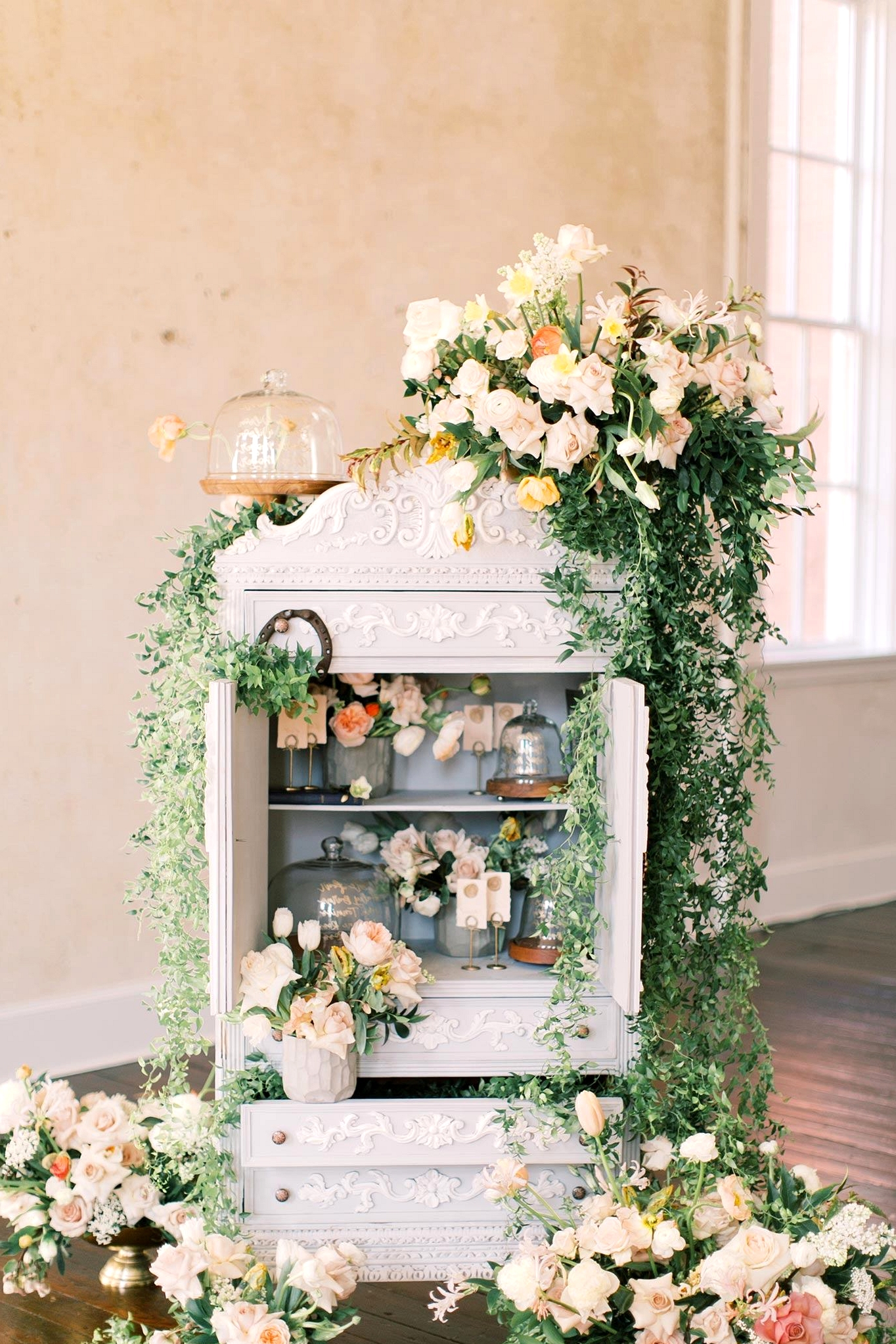 calligraphed cloche seating chart in a shabby chic bookshelf with greenery and fresh flowers