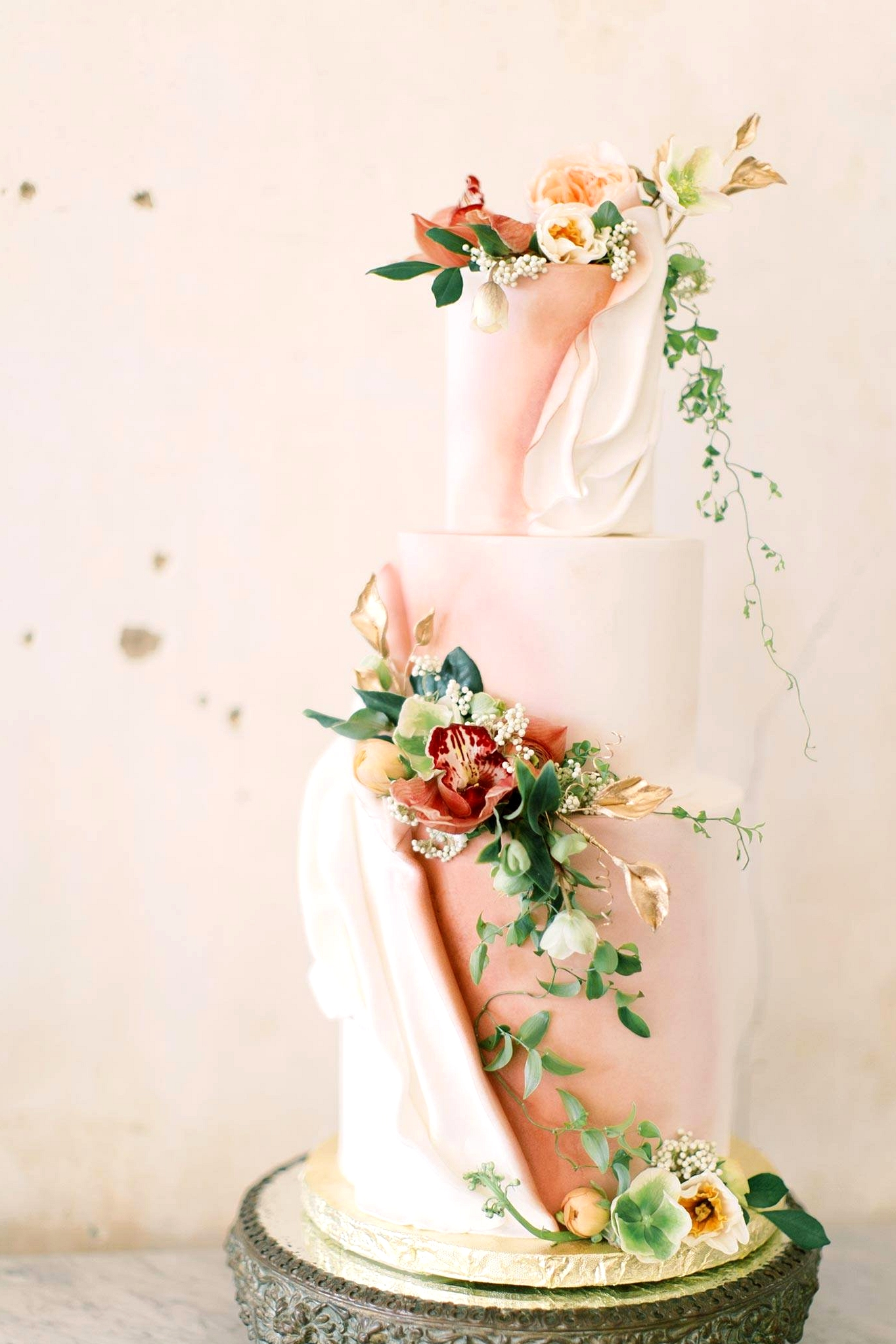 draped fondant wedding cake with pink and white colors and fresh trailing flowers