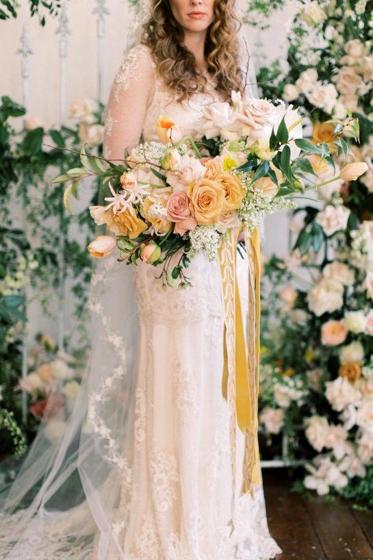 lush floral gate wedding backdrop with bride in a vintage-inspired wedding dress holding a yellow and white spring bridal bouquet