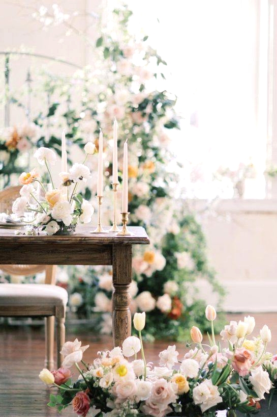 sweetheart table with box flower floor arrangements and a floralized gate backdrop