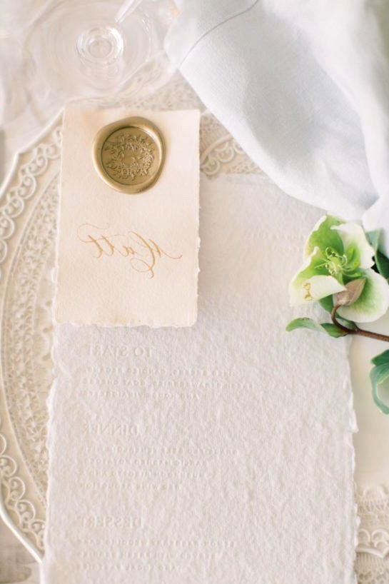 white letterpress menu with a calligraphed place card with a gold wax seal
