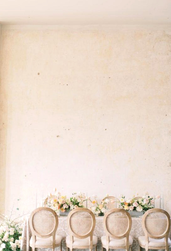 spring wedding table with cane back dining chairs and yellow and cream floral arrangements