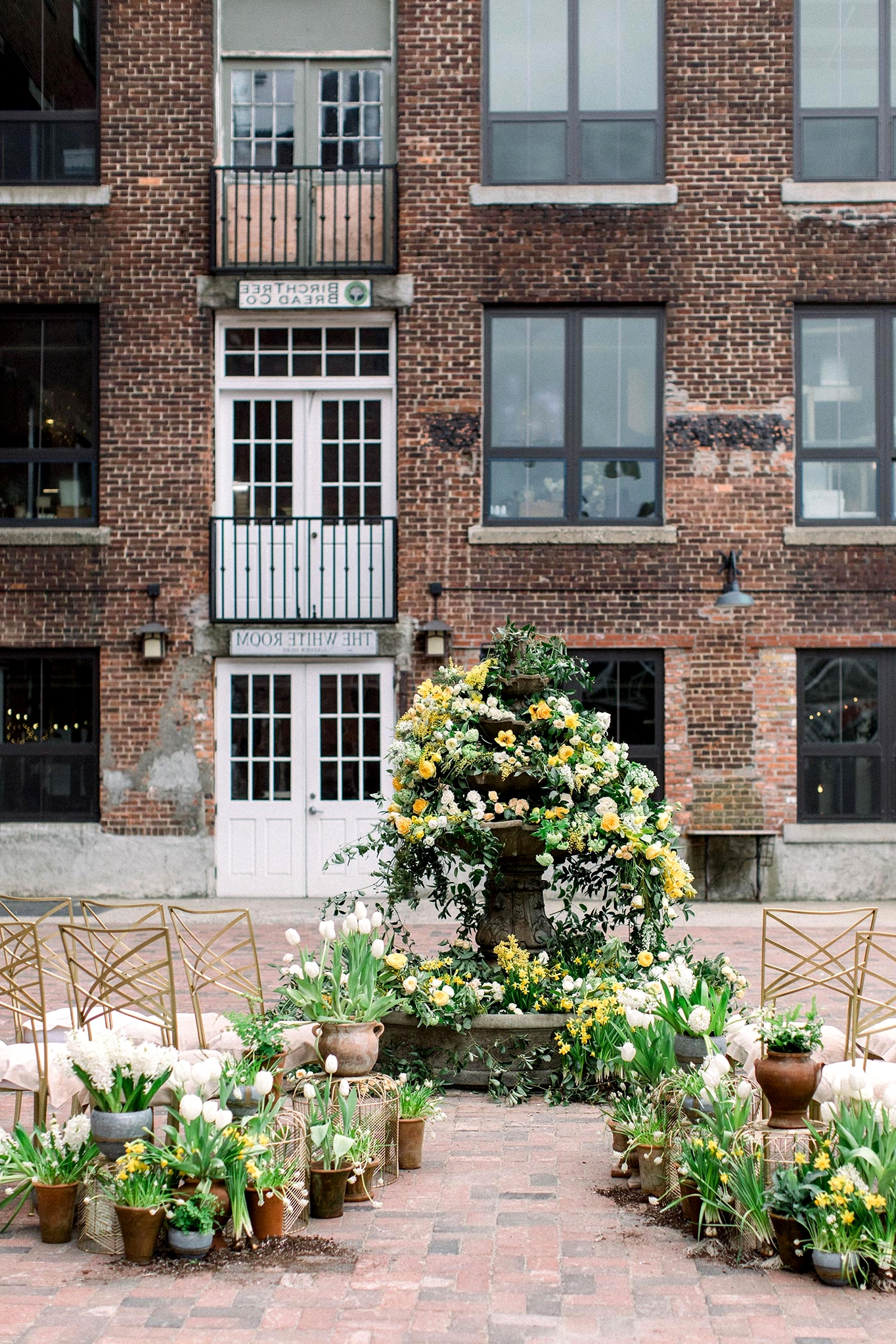 courtyard wedding ceremony with potted plant aisle markers and a floral fountain backdrop