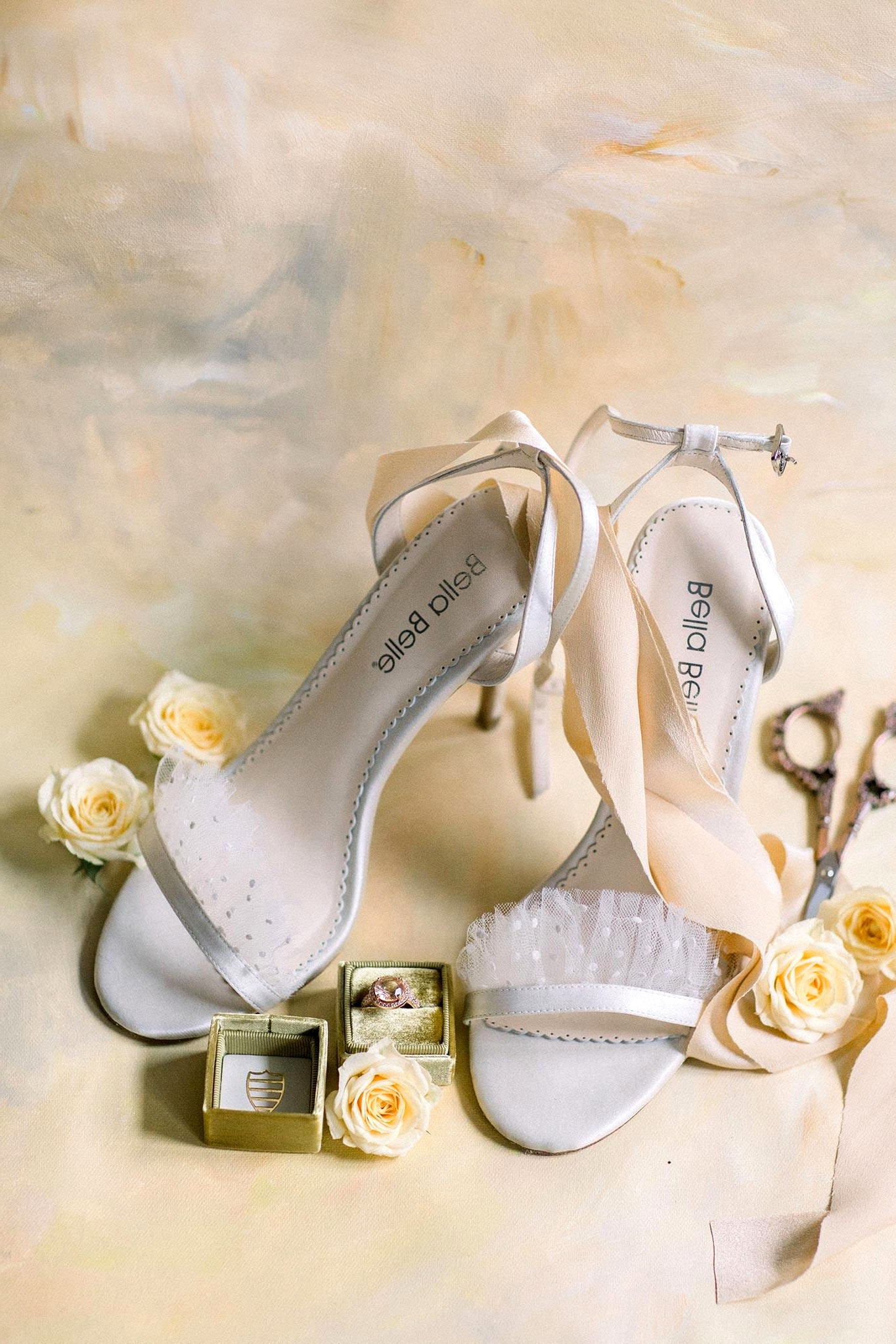 open toed bridal heels with pearl dot ruffled tulle straps and a pink engagement ring in a mustard velvet ring box