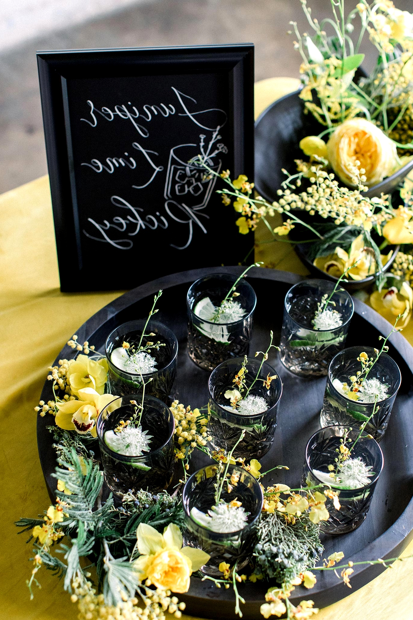 black crystal cut glassware with botanical cocktails on a matte black serving tray with yellow flower accents