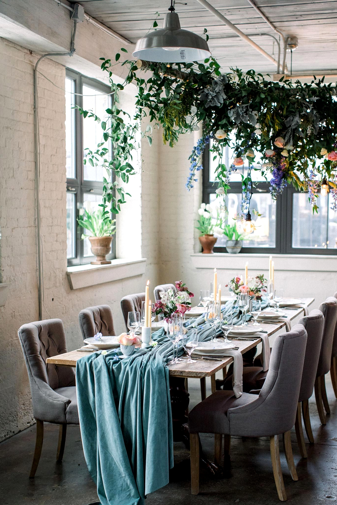 cozy white brick wedding reception with potted plants, a floral canopy and velvet teal table runner
