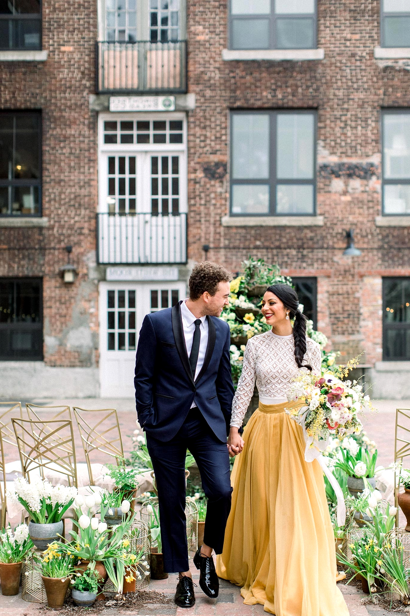 courtyard wedding ceremony with potted plant aisle markers, a floral fountain backdrop, a groom in a navy suit and bride in a two piece wedding dress with a mustard skirt and lace top