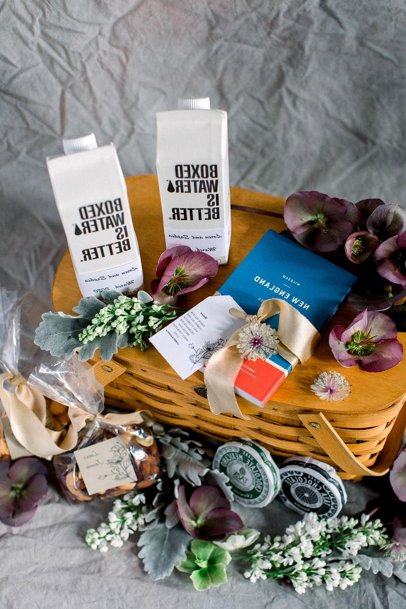 New England wedding welcome basket with boxed water, New England guide, hellebore and more