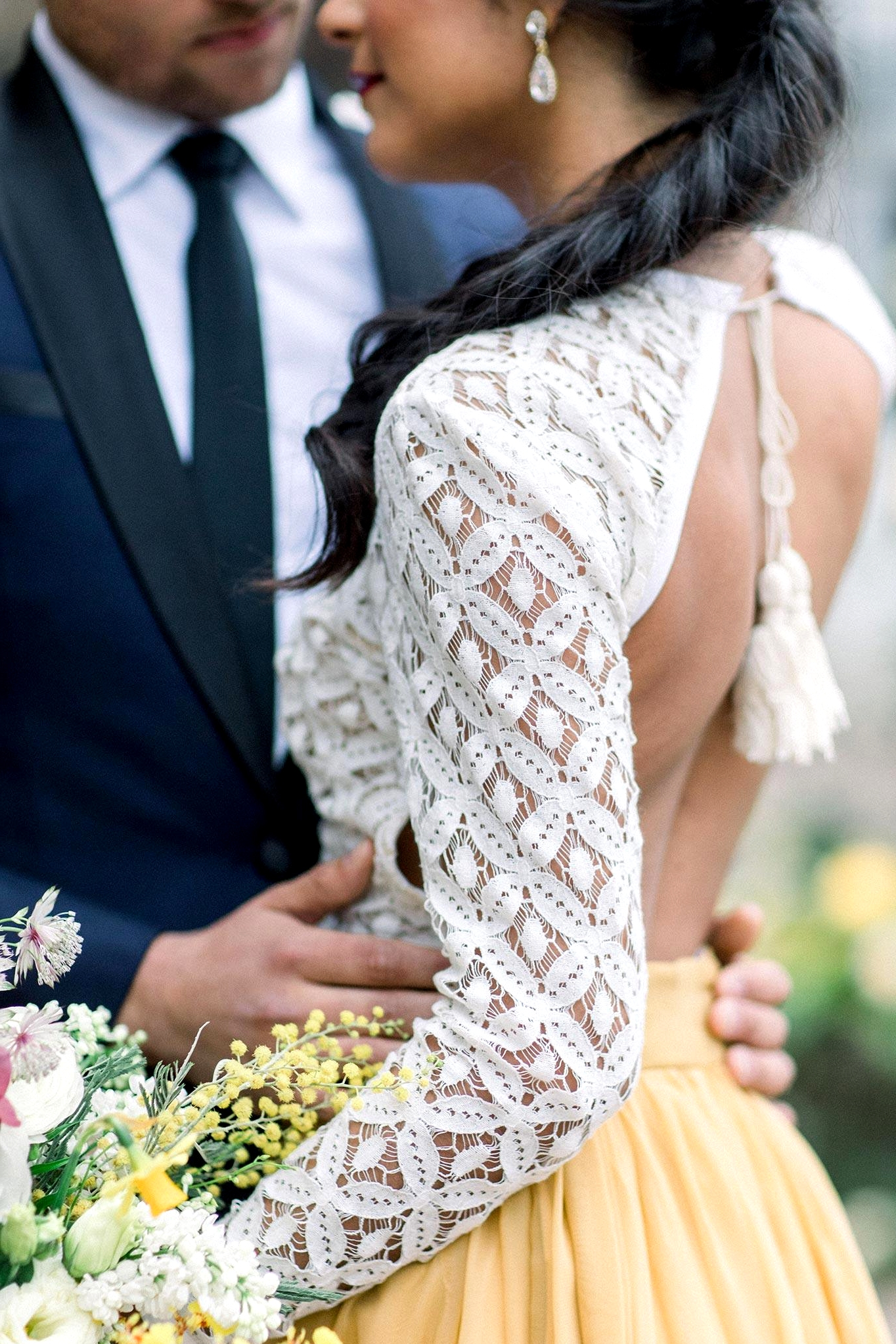 crochet lace top and mustard bridal skirt in this two piece wedding dress look with a colorful spring garden bouquet