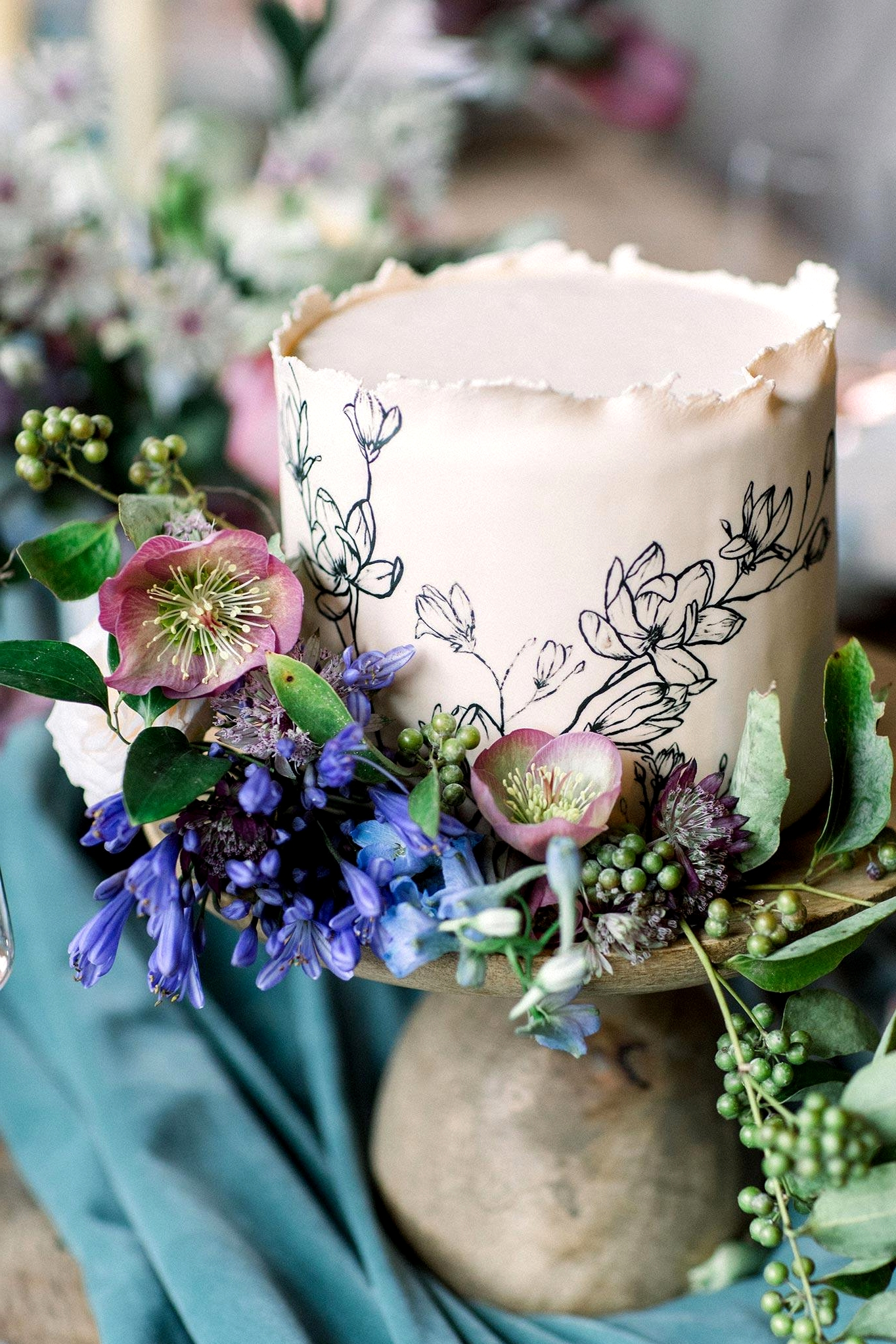botanical sketch wedding cake with fresh flower accents and a wooden cake stand