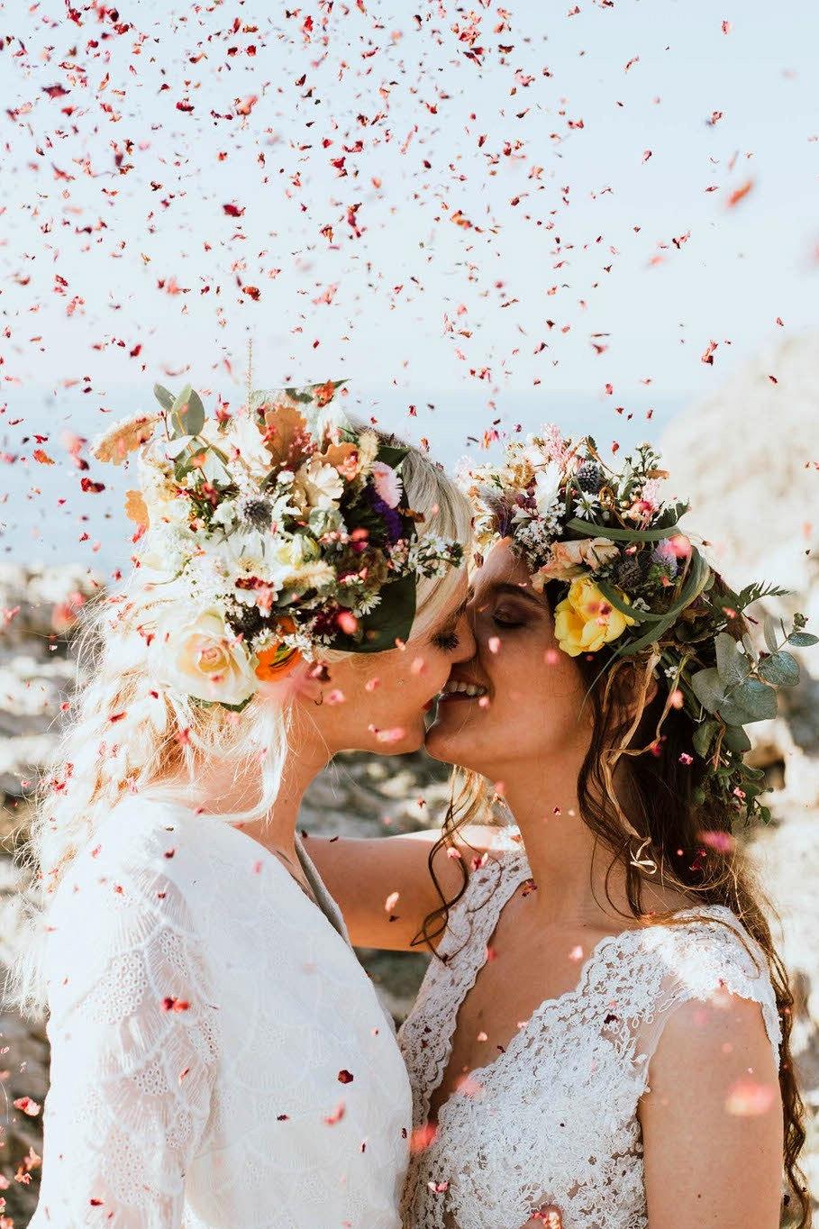 brides kiss as confetti falls around them