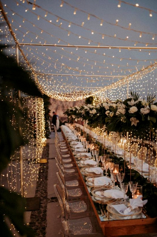 fairy light canopy at the reception begins to glow as it turns to night