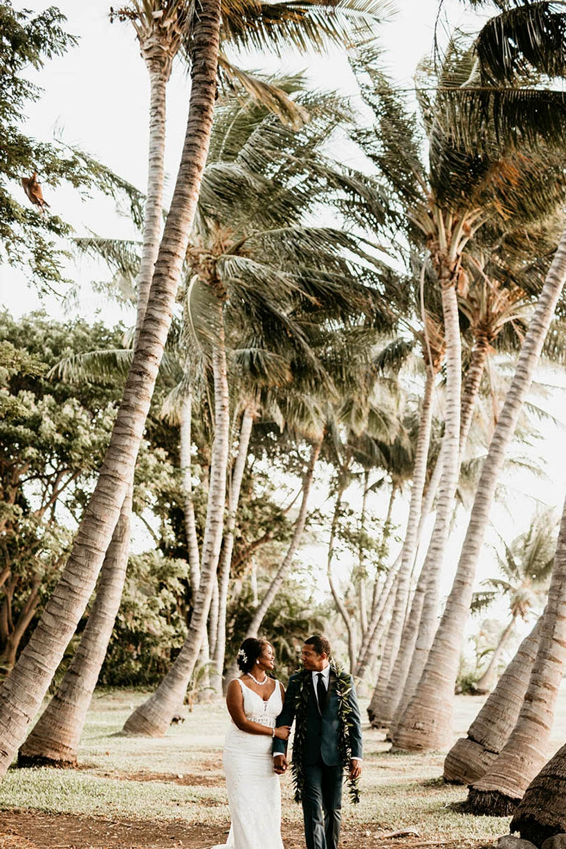 Maui wedding couple portraits beneath palm trees with bride in a v-neck wedding dress and groom with a traditional Hawaiian lei