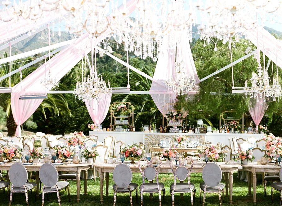outdoor wedding with long table under a clear tent with pops of pink, coral and blue