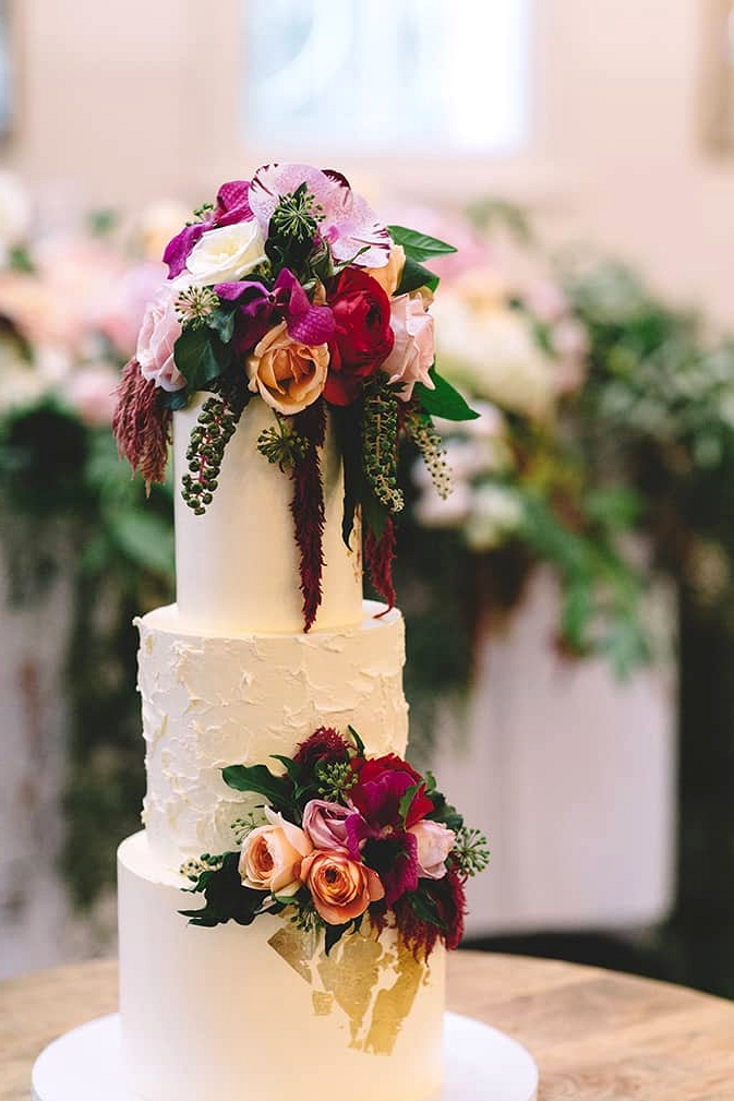 Romantic buttercream wedding cake topped with gold foil, pink roses and orchids | Vanessa Norris Photography