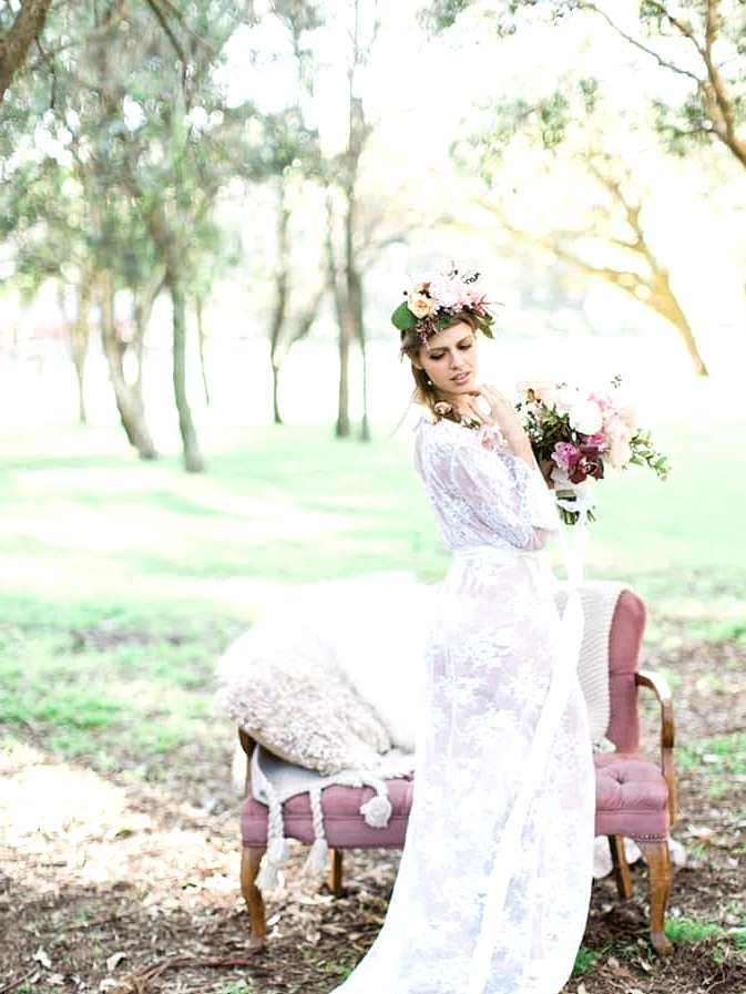 Bohemian bride wearing lace robe with romantic florals