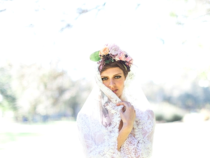 Boho bride wearing lace veil and flower crown