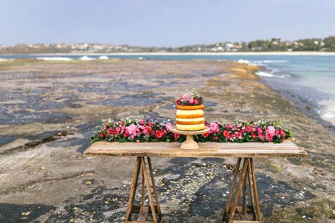 Naked wedding cake on beachside reception table