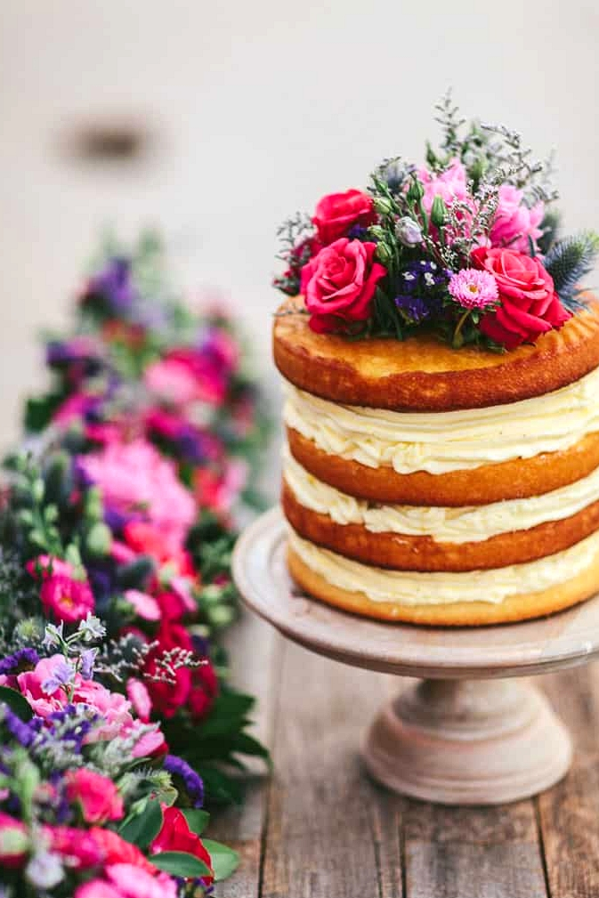 Naked wedding cake with bright floral topper