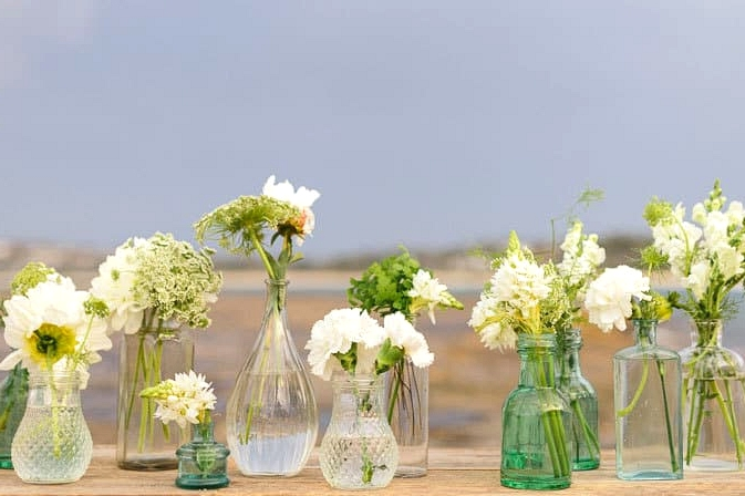 Green and white wedding reception table centrepiece with mismatched bud vases