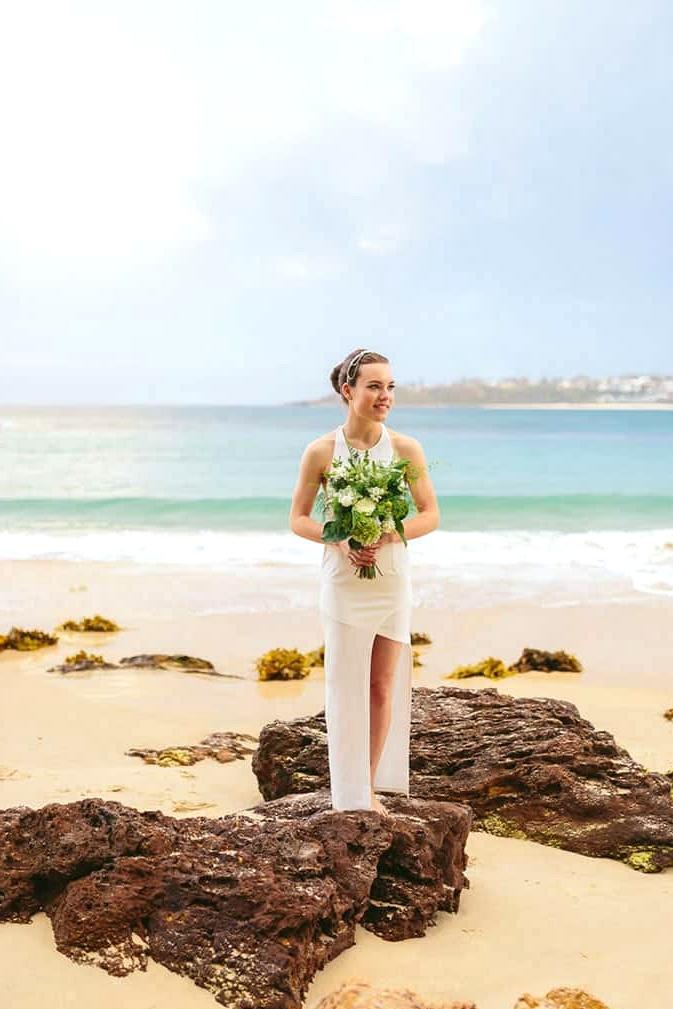 Modern beach bride holding green and white wedding bouquet