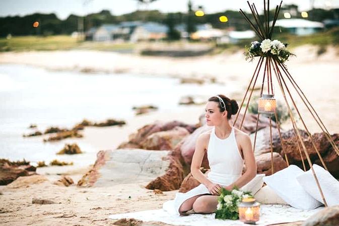 Modern bride sitting in beach wedding teepee