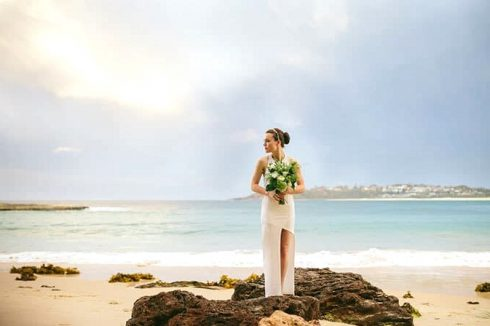 Bride in modern asymmetrical wedding dress standing on beach with bouquet