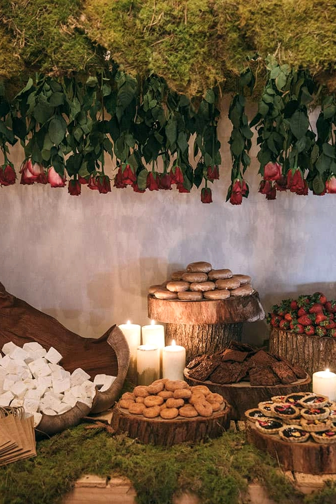 Wedding dessert table styling with moss and wood rounds