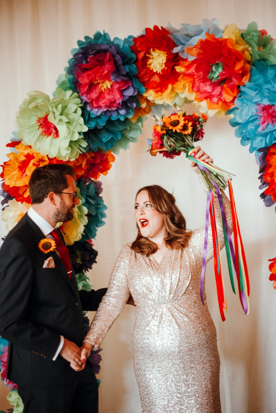Colourful pompom wedding ceremony backdrop |